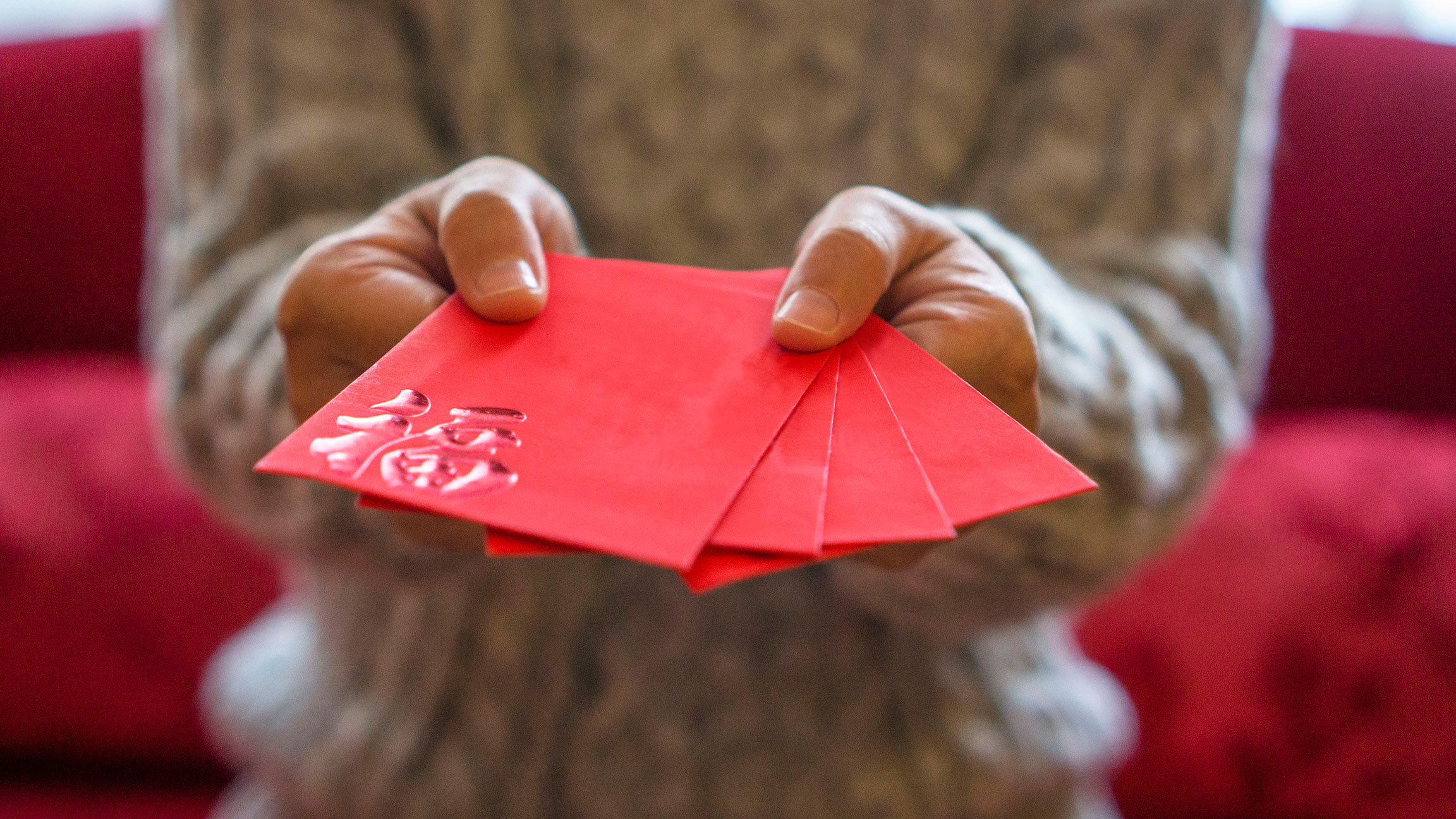 Handing red Chinese New Year envelopes