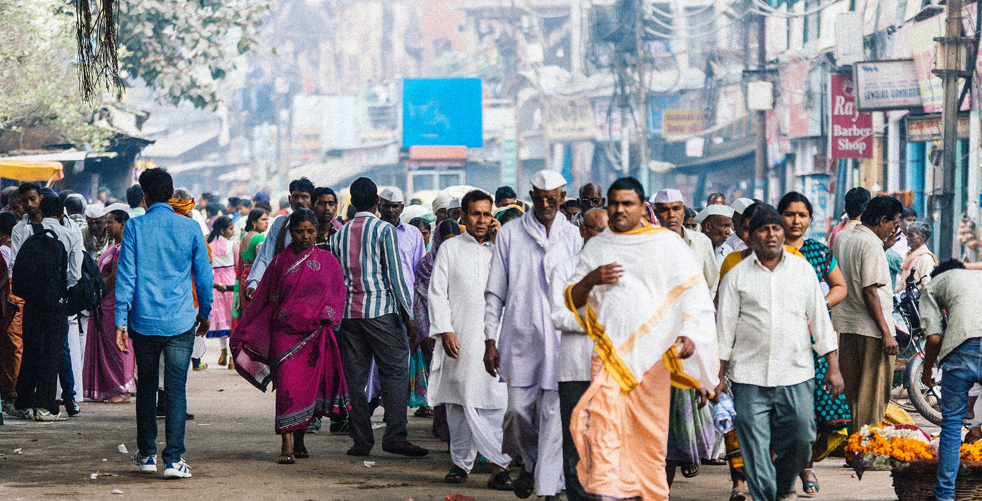 A crowd walks on a street in Varanasi, India