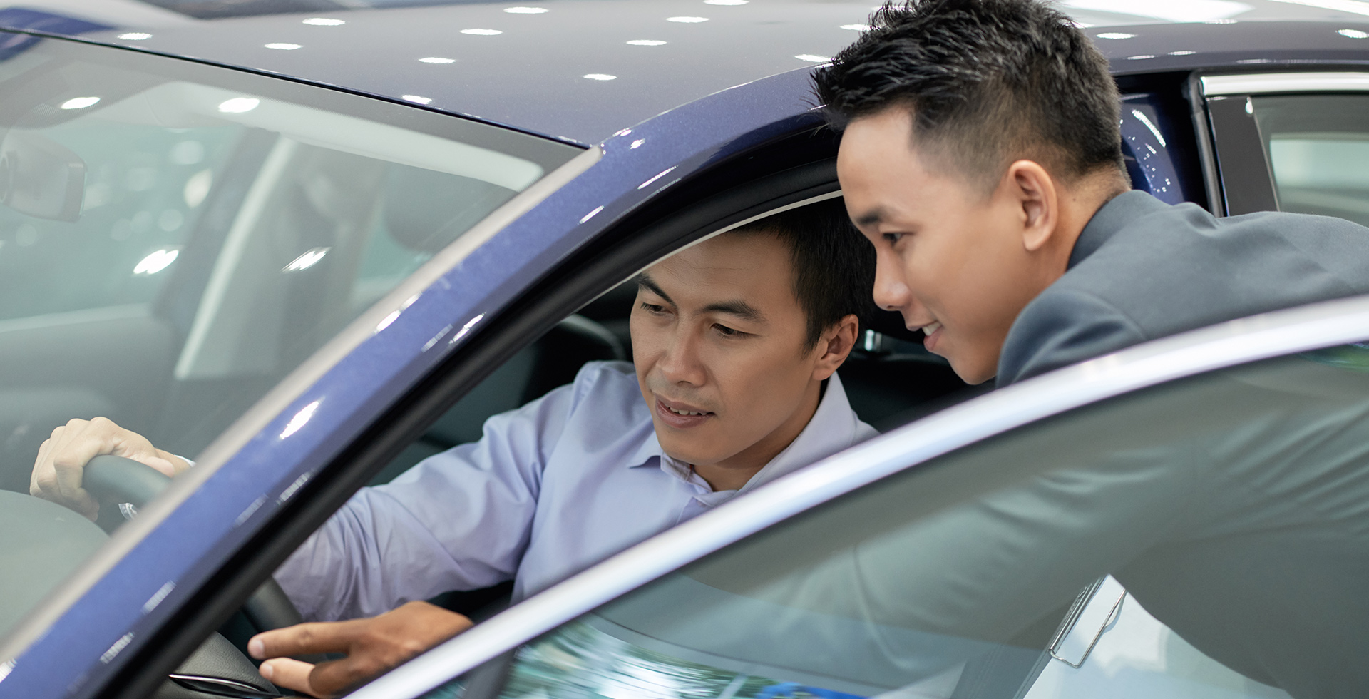 Chinese salesman and customer inspect a new car