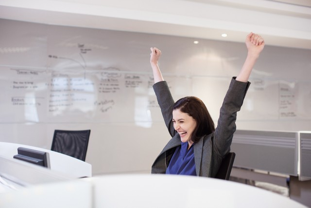 Woman raising her arms in victory at her desk
